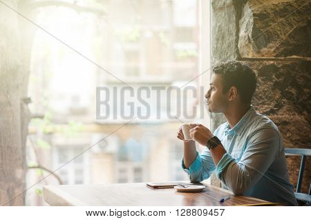 Attractive young man is enjoying a cup of coffee in cafe. He is sitting at table near his tablet. The man is looking though the window with relaxation and dreaming