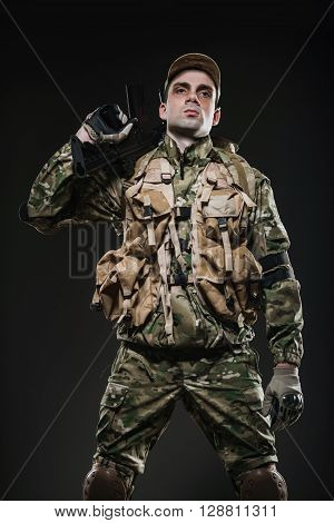 Soldier Man Hold Machine Gun On A  Dark Background