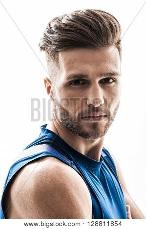 Portrait of handsome strong athlete standing and looking forward seriously. Isolated on background