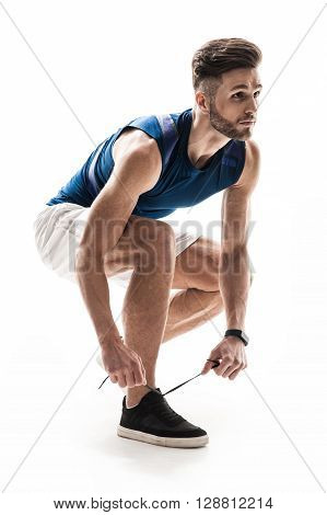 Portrait of handsome young sportsman is tying shoelaces.  He is kneeling and looking forward with seriousness. Isolated