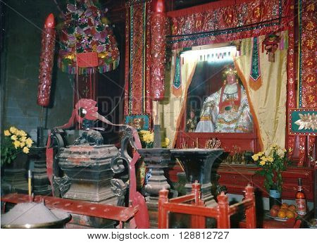 MACAU - CIRCA 1987: An idol sits on an altar inside the A-Ma Temple, built in 1488, and dedicated to Matsu, the goddess of seafarers and fishermen.