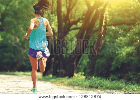 young fitness woman runner running in forest