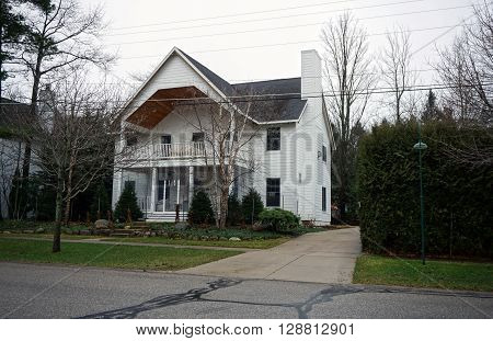 HARBOR SPRINGS, MICHIGAN / UNITED STATES - DECEMBER 23, 2015: A large home with a balcony and a front porch on Second Street in Harbor Springs.