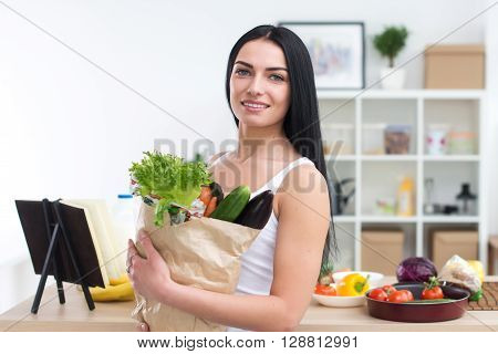 Female cook holding bag full of greens, just came back from market, ready to prepare healthy food with cookbook recipe, close-up front view portrait