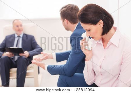 Young married couple is consulting a psychotherapist. The woman is sitting and crying with insult