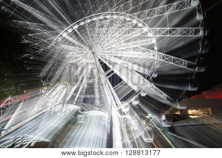 Abstract motion and zoom blur of rotatinmg ferris wheel at night on Brisbane South Bank Australia