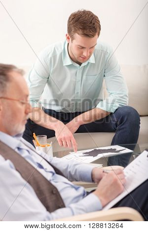 Young man is talking with a psychologist. He is sitting on sofa and hanging head down with desperation. The doctor is writing with seriousness