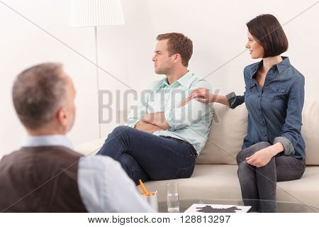 Married family is sitting on couch in psychologist office. The man is looking aside with insult. His wife wants reconciliation. She is touching male shoulder and smiling