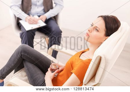 Pretty young girl is consulting a psychotherapist. She is sitting on chair and looking forward with desperation. The man is listening and writing