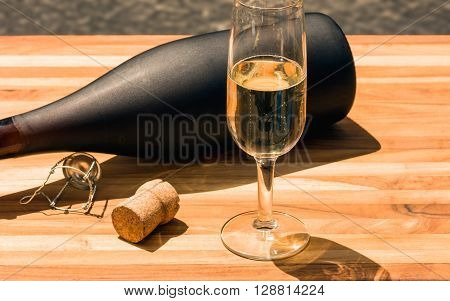 Champagne bottle and flute with cork on a teak board