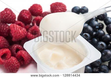 Extreme close-up image of fruit yogurt with fruits around