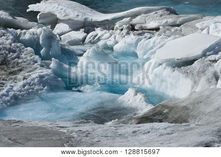 Glacier melting water in blue ice frozen mountain melt
