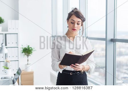 Female office worker writing down notes and day plan in her notebook, standing at workplace, front view portrait
