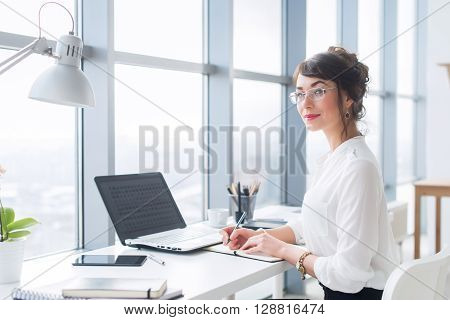 Portrait of a female writer working at office, using laptop, wearing glasses. Young employee planning her work day, writing in notebook