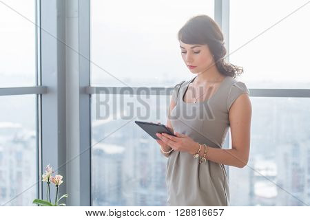 Businesswoman standing in loft light room, typing, reading e-mail, browsing information on-line, using applications on her tablet computer