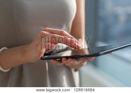 Close-up photo of a businesswoman with digital tablet in hands. Female hands typing, texting and messaging, using wireless internet connection