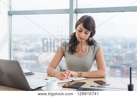 Young female clerk sitting at modern office making notes in her notepad. Employee working on the work table with different digital devices