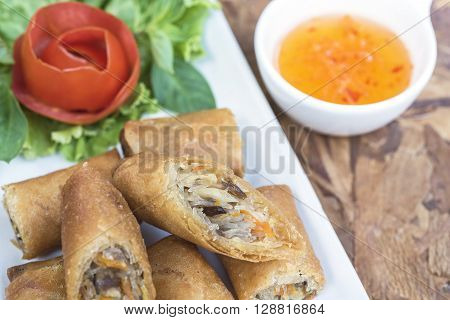 Spring roll vietnamese cuisine in Thai style with sweet suace on wooden table