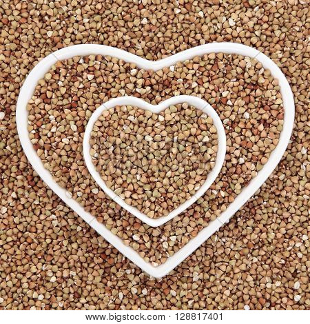 Buckwheat super food in heart shaped bowls forming an abstract background.