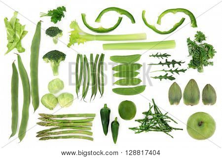 Green fresh vegetable and fruit selection over white background, high in antioxidants and vitamins.