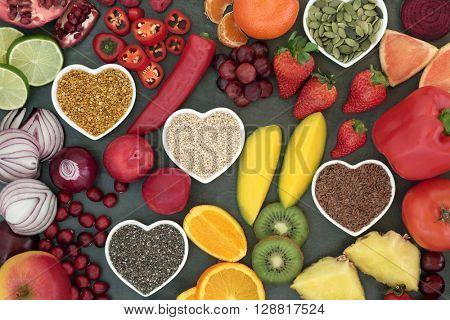 Paleo diet health and super food of fruit, vegetables, nuts and seeds in heart shaped bowls on slate background, high in vitamins, anthocyanins, antioxidants, dietary fiber and minerals.