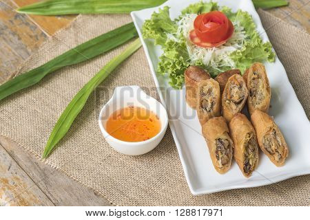 Egg roll vietnamese cuisine in thai style with sweet suace on wooden table