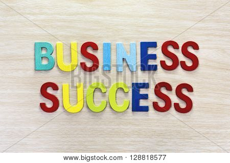 Business success in multicolor on wooden table Letter spelling business success. Business success concept