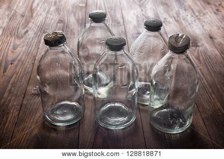 Top View Of Dirty Empty Vintage Transparent Glass Bottles With Stopper On Wooden Deck Background