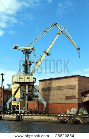 A Yellow cargo container crane at harbor