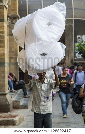 MUMBAI, INDIA - OCTOBER 9, 2015: Unidentified man carryng weight on his head. People have carried burdens balanced on top of the head since ancient times usually to do daily work.