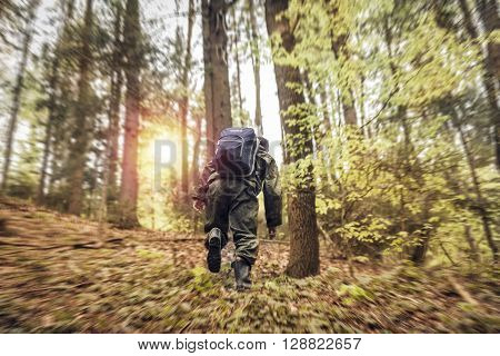 Male guy hiking with blue bag in forest ** Note: Shallow depth of field