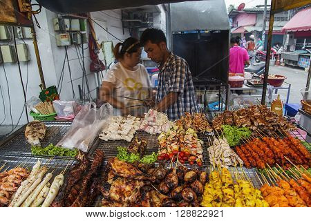 KO PHA NGAN, THAILAND - FEBRUARY 7, 2016: Unidentified sellers of thai food. Street food is a quintessential part of the Thai experience.