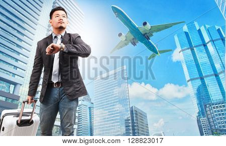 business man and belonging luggage watching to sky and hand watch against high building skyscrapers and passenger plane flying above use for aircraft air transportation traveling of people theme