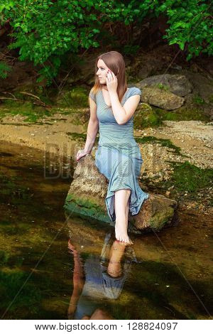 Attractive young woman with long hair wearing casual dress sitting on the rock with feet in a weedy pond water