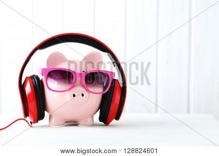 Headphones On Piggybank On White Wooden Table