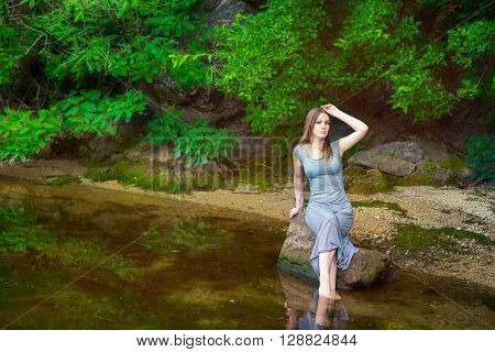 Beautiful young woman with long hair wearing casual dress sitting on the rock with feet in a weedy pond water
