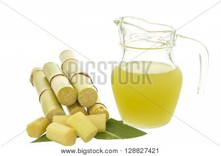 Fresh squeezed sugar cane juice in jug with cut pieces cane isolated on white background