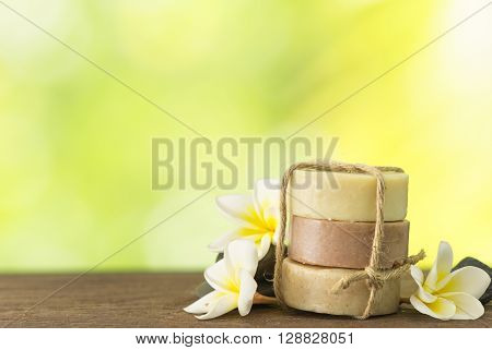 coconut soap mangosteen soap rice milk soap placed on a wooden table with frangipani and natural background. Spa concept.