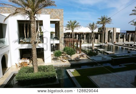 HERAKLION, CRETE, GREECE - MAY 13, 2014: The blue sky swimming-pool modern building with columns and palms in luxury class hotel Grecotel Amirandes on the Mediterranean coast of Crete, May 13, 2014, Greece.