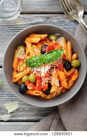 Penne Pasta In Tomato Sauce With Olive And Parmesan On Wooden Table