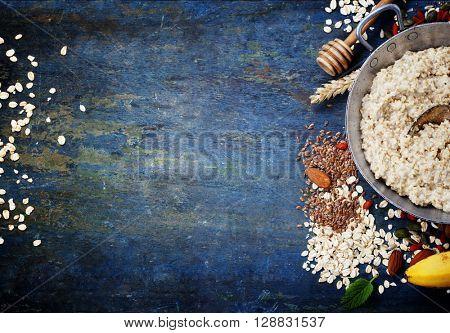 Healthy breakfast. Home made oatmeal porridge, goji berries, banana, pumpkin and chia seeds  in a metal bowl on wooden rustic background.