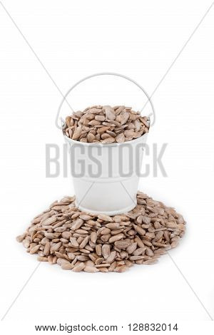 White bucket full of sunflower seeds stands on a heap sunflower on a white background