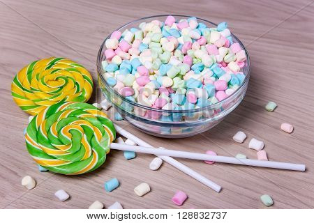 Colorful Mini Marshmallows And Lollipops On Wooden Table