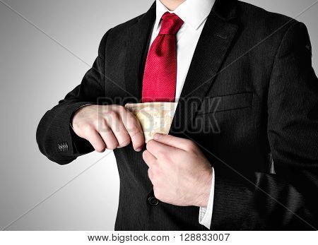 Businessman with red tie puting stack of fifty euro bills into his suit.