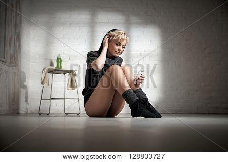 Female dancer sitting on floor, using mobilephone, smiling.