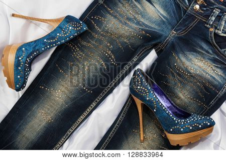 Glamorous women's fashion shoes in rhinestones lying on jeans view from above