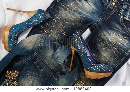 Glamorous women's fashion shoes in rhinestones lying on jeans and denim jacket view from above