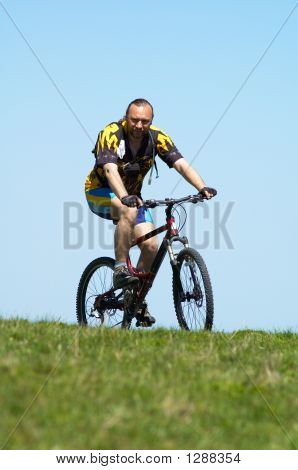 Mountain Biker, Sky And Grass