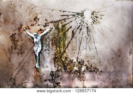 Metal crucifix on an old white marble plate with symbolic sun on it