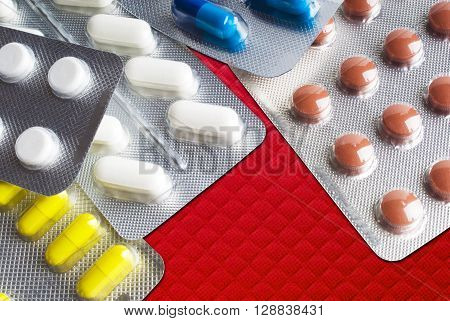 Capsules and pills packed in blister close-up background.